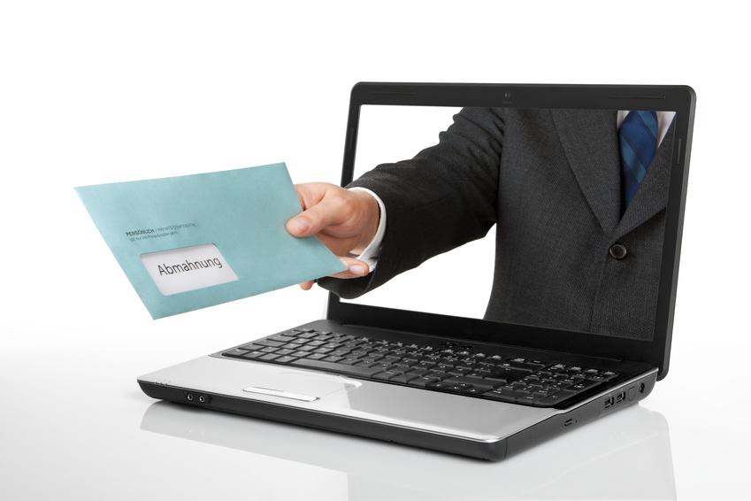Foto eines Abmahnungsbriefes, welcher durch den Bildschirm eines Notebooks gereicht wird