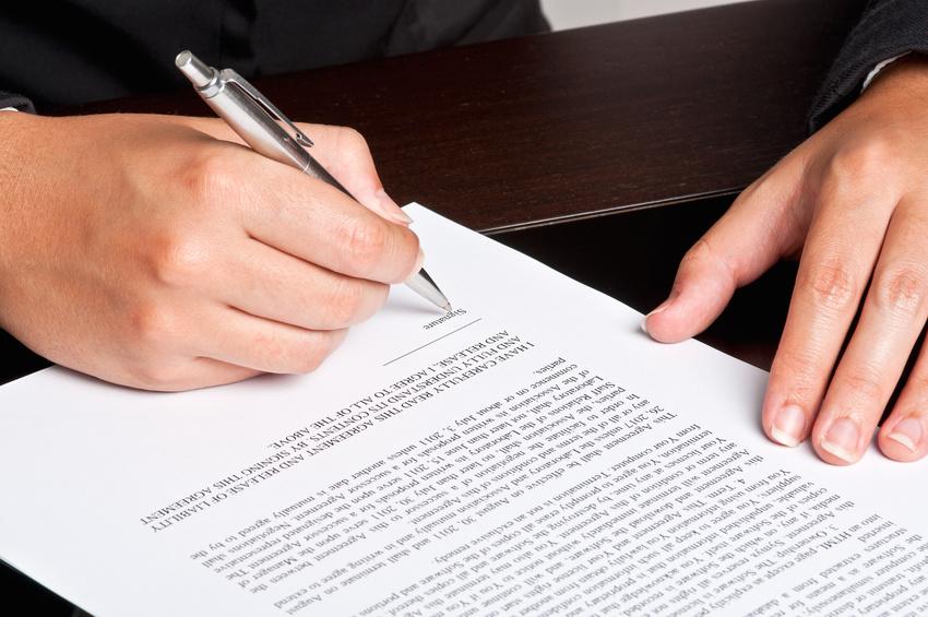 Foto einer Person welche ein Dokument unterschreibt